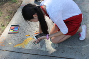 A participant in the Chalk Art Drawing Contest work on her submission.